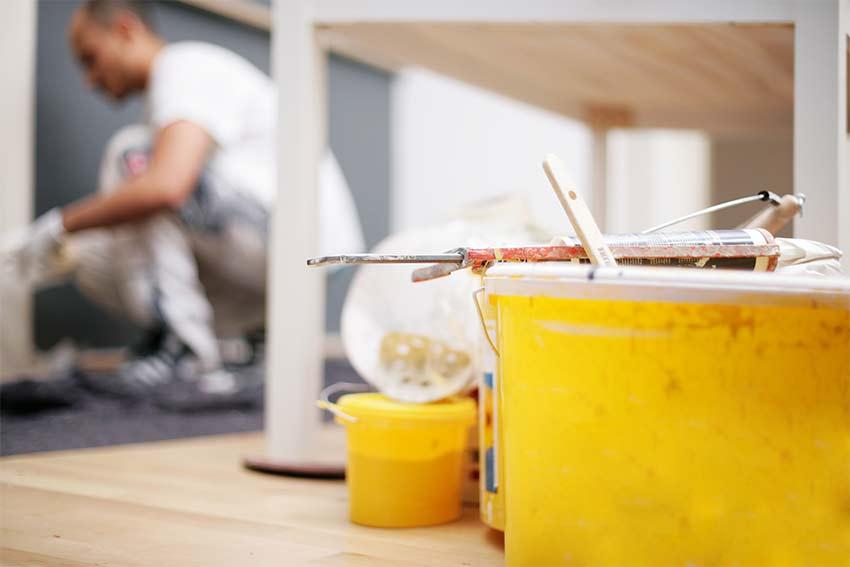 Gelber Farbeimer im Vordergrund, im Hintergrund ein Maler bei der Arbeit