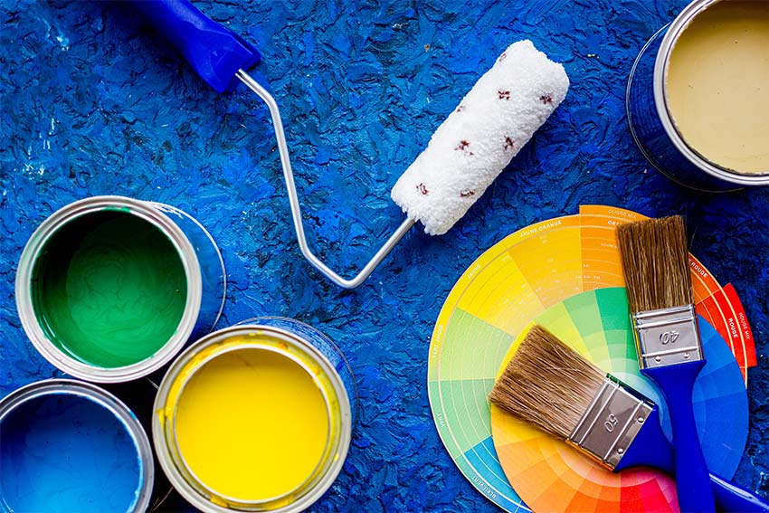 Colorful paints and brushes on blue wooden desk background top view